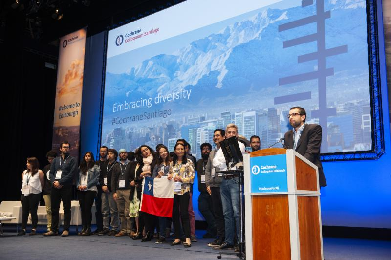 "Group of Cochrane Chile members stand on stage at Edinburgh Colloquium with screen behind them showing a picture of Santiago and reading ""Embracing Diversity"""